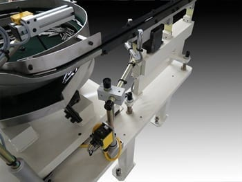 A photoelectric sensor monitors the parts level in the bowl feeder.